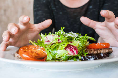 Woman attacks medallions with salad, hunger and impatience concept. Grilled meat, tomatoes, eggplant and green ruccola with grated cheese, close up picture Stock Photo