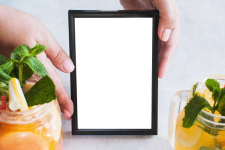 tenderly: Picture frame tenderly holding by hands with fresh fruit cocktails in front. Food blogs, menu and recipes for web sites of cafe and restaurant, close up picture with copy space