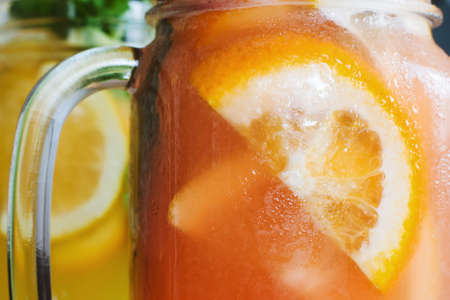 Background of fresh cold strawberry cocktail in jar. Close up picture of glass wall of fruit drinks with drops of water, sliced orange shape and mint, refreshment and coolness concept