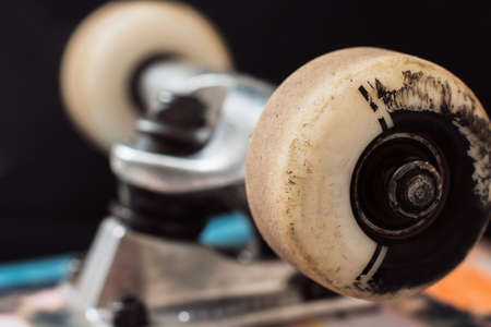 Close up skateboard truck and wheels on black background. Repairing of professional extreme sport devices and skateboarding elements. Chassis, kingpin, bushing, hanger