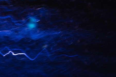 Abstracte achtergrond van witte en blauwe golven in beweging op zwart. Bokeh van onscherpe bochten, wazige neonleds, vergelijkbaar met elektriciteit en stroom, achtergrond van blikseminslag en magneetveld