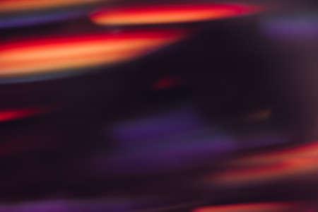 デフォーカスライトモーションブラーの抽象的な背景。輝く都市の背景には、キラキラ光る紫、オレンジ、赤い線の壁紙、夜の街の led ボケ