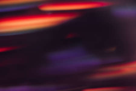 Abstract background of defocused light motion blur. Glowing urban backdrop, sparkle shiny purple, orange and red lines wallpaper, night city leds bokeh