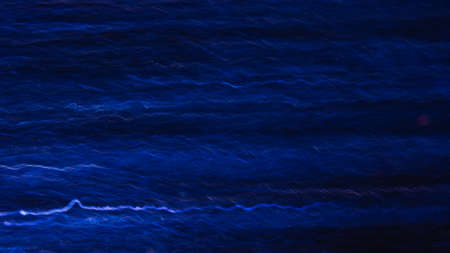 Abstract background of white and blue waves in motion on black. Bokeh of defocused curves, blurred neon leds, similar to electricity and power, backdrop of lightning strike and magnet field