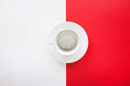 Empty tea or coffee cup with saucer isolated on red and white background, serving table, top view picture Stock Photo