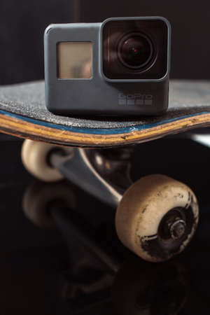 Kharkov, Ukraine - June 29, 2017: Camera GoPro Hero5 staying on skateboard on black glance background. Professional extreme sport devices and action shooting of competitions and training, free space