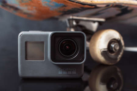 Kharkov, Ukraine - June 29, 2017: GoPro Hero5 stays near skateboard on black glance background. Professional camera for action shooting of extreme sport competitions and training, close up Editorial