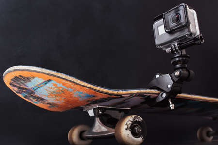 Kharkov, Ukraine - June 29, 2017: GoPro Hero5 fixed on professional skateboard on black background. Video shooting of tricks and extreme sport competitions, free space