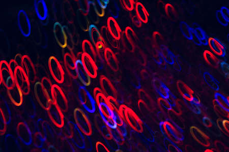 Abstract background of colorful ellipses in motion on black. Bokeh of defocused curls, blurred neon blue, red and yellow leds, glowing festive backdrop of night city lights