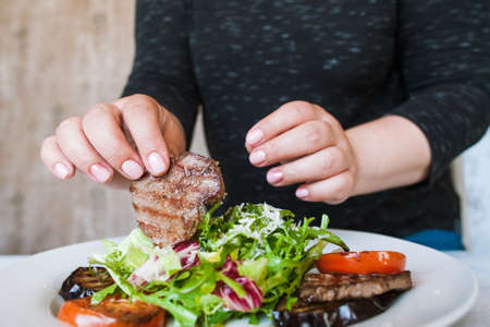 Woman starts to eat medallions with salad. Grilled meat, tomatoes, eggplant and green ruccola with grated cheese, hunger and impatience, close up picture Stock Photo