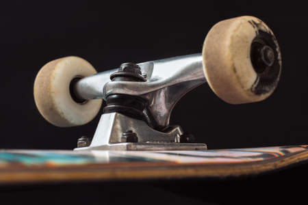 Close up of skateboard truck and wheels on black background. Advertizing safety construction of professional extreme sport devices and skateboarding elements. Axle, kingpin, bushing, hanger