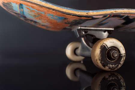 검은 눈 배경에 부분적으로 본된 스케이트 보드입니다. 전문 극단적 인 스포츠 장치의 문질러 진 갑판 및 바퀴, 안전 consrtuction 및 요소의 마찰 견뢰도