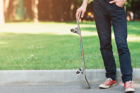 Unrecognizable man with skateboard in hands. Extreme sport challenge and competition, readiness for adventure and self-confidence. Skateboarding background with free space, urban lifestyle and culture Stock Photo