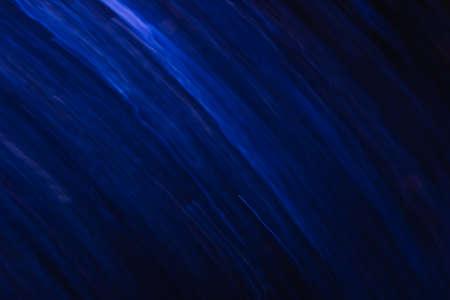 黒の動きで白と青の線の抽象的な背景は。多重曲線のボケ味がぼやけてネオン led、恒星システム、銀河、彗星と星の背景に似ています