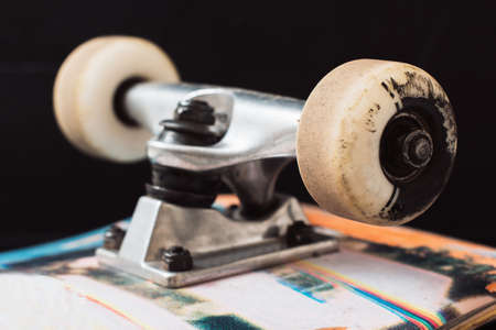 Close up skateboard truck and wheels on black background. Professional extreme sport and skateboarding elements, axle, kingpin, bushing, hanger