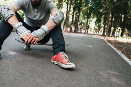 ハード競技後のプロスケーター。極度なスポーツの挑戦および訓練、枯渇およびリフレッシュメントの概念。スケートボーダー現代都市のライフス 写真素材