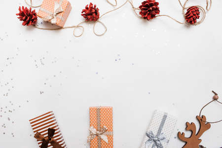 Festive background of Christmas holiday. Gift boxes on white background with silver star tinsels and strobila decoration above, top view with copy space. Celebrations, New Year, festival concept Stock Photo