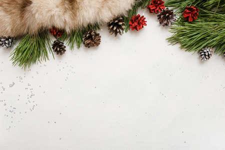 겨울 휴가 장식의 축제 배경입니다. Strobila 및 모피 흰색 배경, 상위 뷰 및 복사 공간 소나무 분기. 축하, 새해, 크리스마스, 가정 및 레스토랑 장식 개념 스톡 콘텐츠