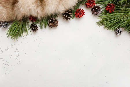 Festive background of winter holidays decoration. Pine branch with strobila and fur on white backdrop, top view and copy space. Celebration, New Year, Christmas, home and restaurant decor concept