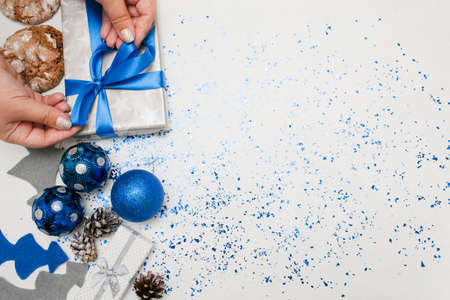 Preparing Christmas decor and gifts top view. Woman binding present by festive tape, ornament blue balls, felt fir tree, cakes and tinsel spread around with copy space. Handmade decoration concept Stock Photo