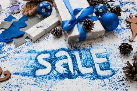 Grote verkoop op kerst- en nieuwjaarsvakantie. Close-up verpakte cadeaus en verschillende handgemaakte ornamenten met informatieve inscriptie eronder. Feestelijk en kleurrijk concept als achtergrond Stockfoto - 86501423