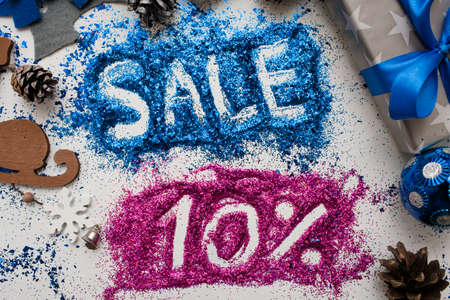 Sales on Christmas and New Year holidays, top view close up. Colorful decoration with informative inscription of 10 pct discount for shop-windows, shopping malls and advertizing background concept Stock Photo