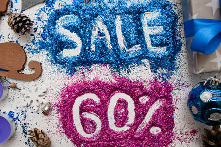 Sales on Christmas and New Year holidays, top view close up. Colorful decoration with informative inscription of 60 pct discount for shop-windows, shopping malls and advertizing background concept Stock Photo