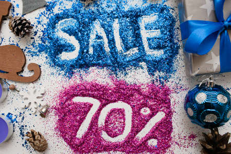 Sales on Christmas and New Year holidays, top view close up. Colorful decoration with informative inscription of 70 pct discount for shop-windows, shopping malls and advertizing background concept