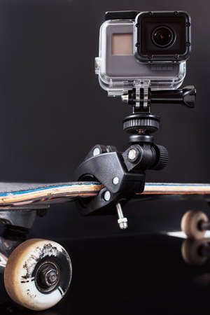 Kharkov, Ukraine - June 29, 2017: GoPro Hero5 for professional video shooting of extreme sport tricks, training and competitions. Action camera fixed on skateboard on black background with free space Editorial