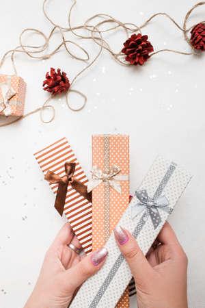 새 해 휴일의 축제 배경입니다. 선물 상자 손 및 손수 만든 장식 인근, 상위 뷰를 들고. 축하, 크리스마스, 축제 및 paperpresents 개념