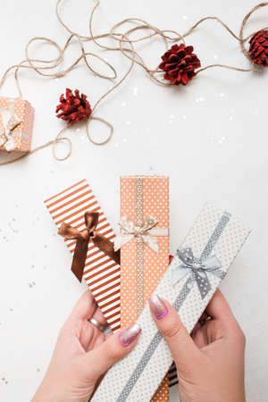Festive background of New Year holiday. Gift boxes holding in hands and handmade decoration nearby, top view. Celebrations, Christmas, festival and paperpresents concept