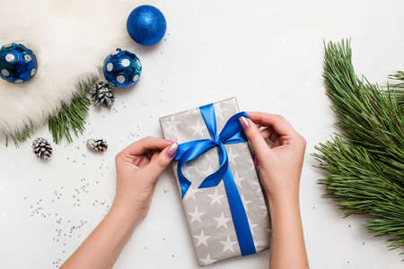 Festive background of Christmas present decoration. Unrecognizable woman wrapping gift box, ornament blue balls and pine branch laying on table nearby, top view with copy space. Handmade decor concept Stockfoto