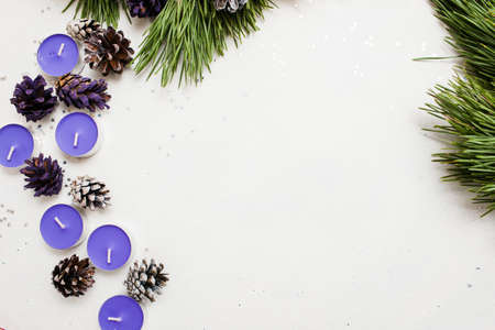Festive background of New Year decoration. Small lavender tea candles with pine branch and strobila, top view and copy space. Holiday preparation, home and restaurant decor concept Banco de Imagens