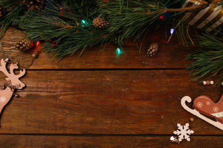 Festive background of winter holidays decoration. Pine branch, fairy lights and handmade ornaments on wooden table, top view copy space. Celebration, New Year, Christmas, homemade decor concept Banco de Imagens