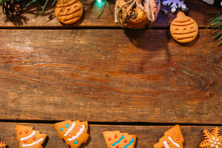 Festive background of Christmas bekary. Top view homemade gingerbread cookies and pine branch on wooden backdrop, free space in middle. Family celebration, New Year traditions and decor concept