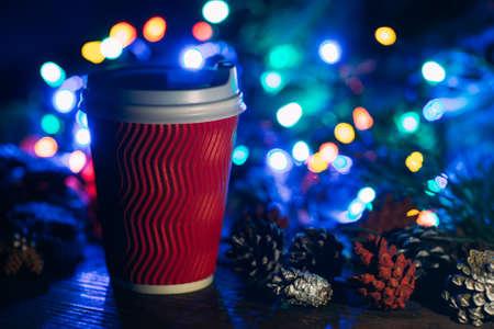 맛있는 크리스마스 축 하 라 떼와. Defocused 요정 조명 배경에 따뜻한 에너지 음료와 strobila 장식 잔을 닫습니다. 카페 및 박람회, 행복 한 휴일 개념에서