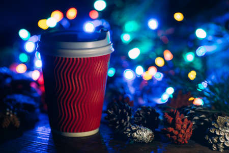 Delicious Christmas celebration with latte. Close up cup of warm energy drink and strobila decoration on defocused fairy lights background. Cozy xmas evening in cafe and fairs, happy holiday concept Banco de Imagens
