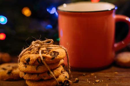 라 떼와 쿠키 맛있는 크리스마스 휴가. 축제 잔 빛 배경에 따뜻한 음료와 달콤한 스콘의 컵을 닫습니다. 행복 한 축 하, 아늑한 크리스마스 저녁 개념 스톡 콘텐츠