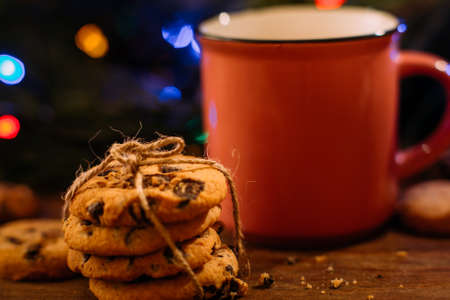 Delicious Christmas holiday with latte and cookies. Close up cup of warm drink and sweet scones on festive fairy lights background. Happy celebration, cozy xmas evening concept