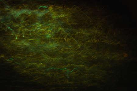 Abstracte achtergrond van gele en groene golven in beweging op zwart. Bokeh van onscherpe crankles, wazige neonleds, vergelijkbaar met elektriciteit en stroom in lampen, achtergrond van bliksem en magneetveld Stockfoto