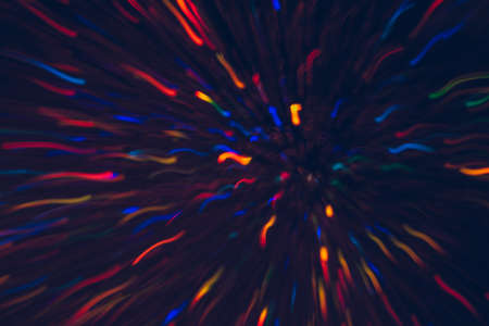 Abstract background of colorful lines in motion on black. Bokeh of defocused blue, yellow and red curves, blurred rainbow neon leds, festive backdrop of holidays, fireworks and celebrations