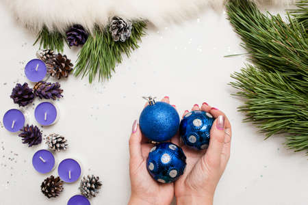 Festive background of Christmas decoration. Small tea candles with pine branch and ornament balls in hand, top view and copy space. Holiday, home decor and celebration concept Banco de Imagens
