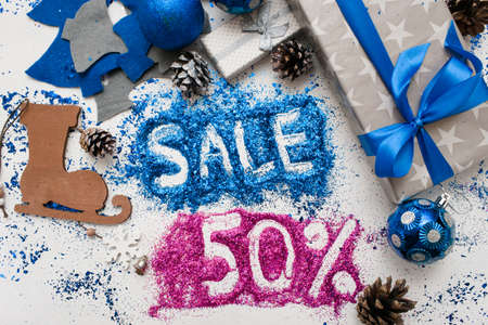 Sales on Christmas and New Year holidays, top view close up. Wrapped presents and different handmade ornaments with informative inscription of 50 pct discount. Festive and colorful background concept