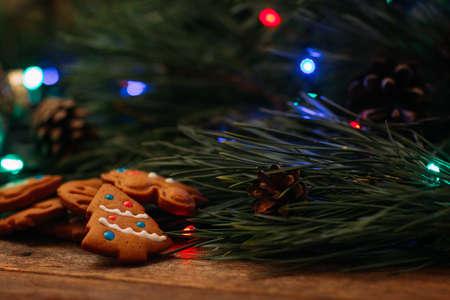 크리스마스 장식의 축제 배경입니다. 요정 조명과 나무 테이블에 수 제 쿠키 소나무 분기를 닫습니다. 가족 축하, 새해 전통과 손수 장식 개념