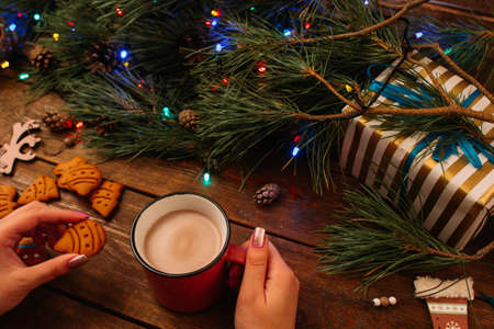 Delicious Christmas holiday with latte and cookies. Decoration from pine, fairy lights and gift box on wooden background nearby, view from shoulder. Happy celebration, warm xmas evening concept
