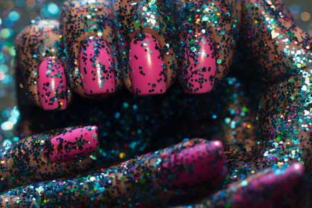 Christmas festive manicure. Close up glittering mermaid hands of woman with pink gel nail polish. Holiday sparkled background, body art, celebration, preparing presents concept Stock Photo