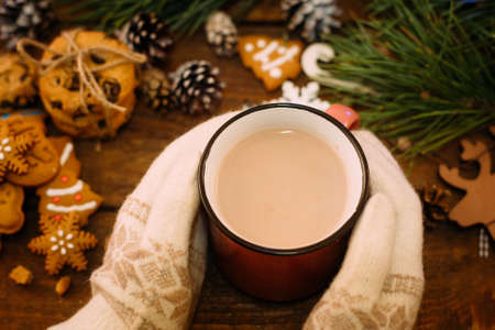 Warm Christmas holiday with latte and cookies. Top view unrecognizable woman with cup of drink in knitted gloves hands on festive background. Cozy xmas evening on festival and fairs concept Banco de Imagens