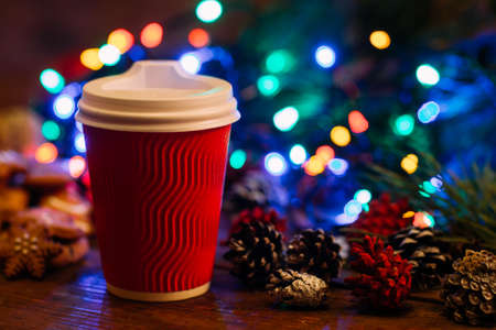 Delicious Christmas with take away latte. Close up cup of warm energy drink and strobila decoration on festive fairy lights background. Cozy xmas evening in cafe and fairs, happy holiday concept