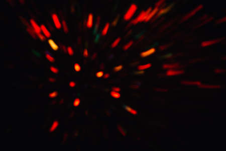Abstract background of colorful lines in motion on black. Bokeh of defocused splashes, blurred yellow and red neon leds, fireworks and salute, space and sky backdrop