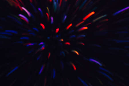 Abstract background of colorful lines in motion on black. Bokeh of defocused splashes, blurred red and blue neon leds, fireworks and salute, space and sky backdrop Banco de Imagens